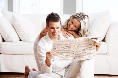 Couple looking at houses in newspaper